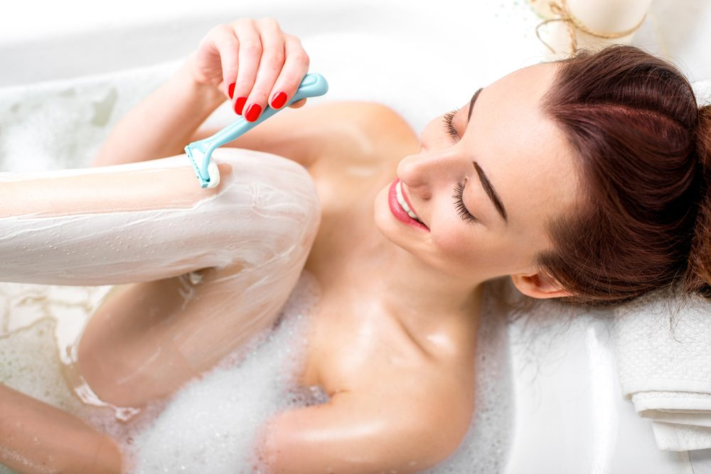 young positive woman shaving her legs
